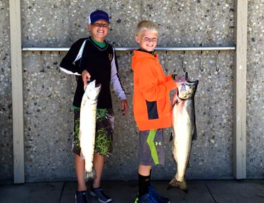 two-young-boys-holding-fish-they-caught-bigger-than-they-are